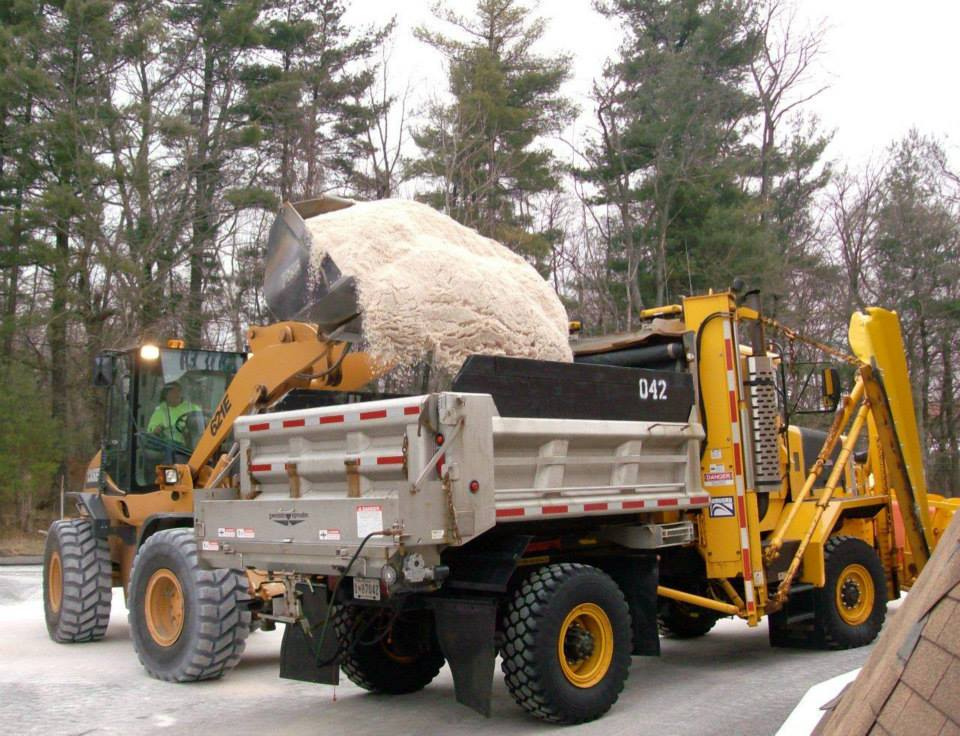 Tractor loading salt into a dump truck.